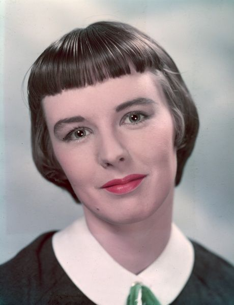 A smiling young woman with a short pageboy hairstyle with a short, thick fringe (bangs) wears a blouse or dress with a peter pan collar