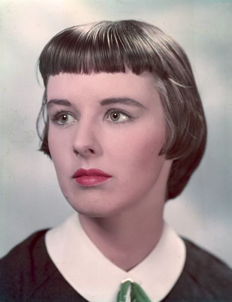A rather doleful looking ingenue with short pageboy hairstyle with a short, thick fringe (bangs) wears a blouse or dress with a peter pan collar