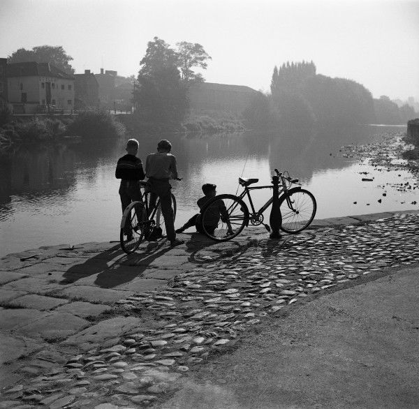 Three boys with their bikes admire the still river in the clear evening light at Bewdley Bridge, Worcestershire. Photograph by Norman Synge Waller Budd