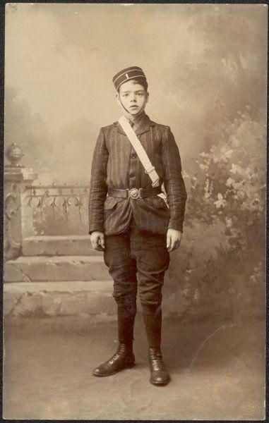 A boy in his Boys' Brigade uniform, posing for a studio photograph with a garden backdrop