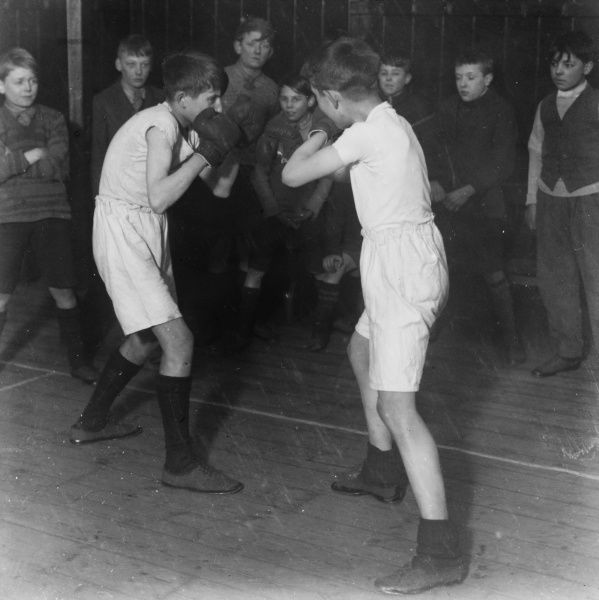 Two boys in boxing gloves engage in a round of boxing during an evening at a Boys Club