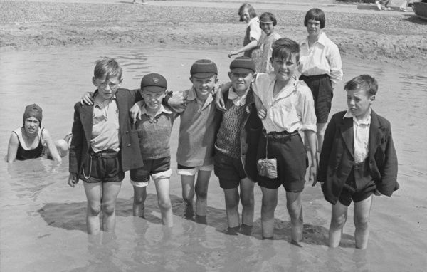 A group of boys and girls play in the sea at Burnham. Six boys stand in a line with their trousers rolled up for a photograph