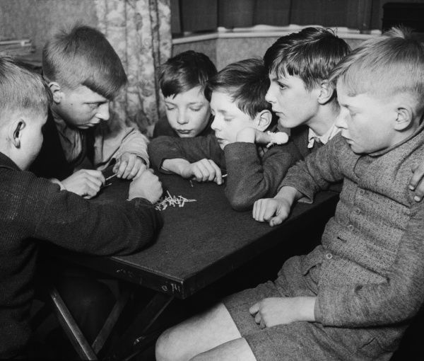 Six boys from a Boys Club sit around a table for a game of what could be Jack Straws or Spillikins