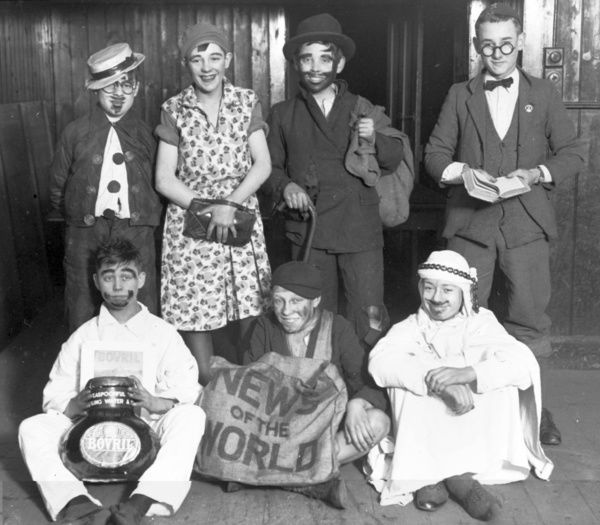 Seven boys from a Boys Club in wonderful fancy dress costume. Characters include, a News of the World paperboy, an Arab, a housewife, and the pajama wearing Bovril character who looks like he has had his face in the jar. Very humorous!