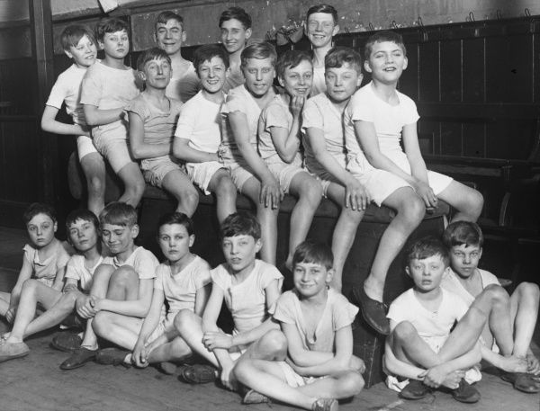 An informal gym class group photograph featuring 19 boys from a Boys Club of 1933, sitting on gym equipment and smiling for the camera