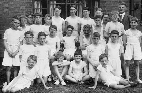 An formal gym class group photograph featuring 24 boys from a Boys Club of 1933, standing and sitting outside, with their club leader standing proudly to the right