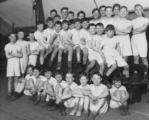 An informal gym class group photograph featuring 32 boys from a Boys Club of 1934, sitting on gym equipment and smiling for the camera