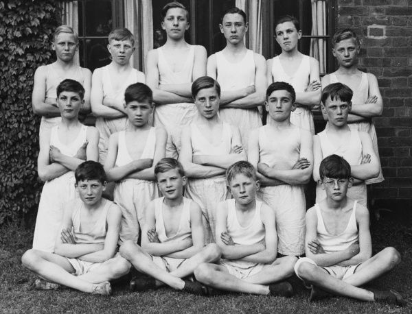 An formal gym class group photograph featuring 15 boys from a Boys Club of 1937, standing and sitting outside