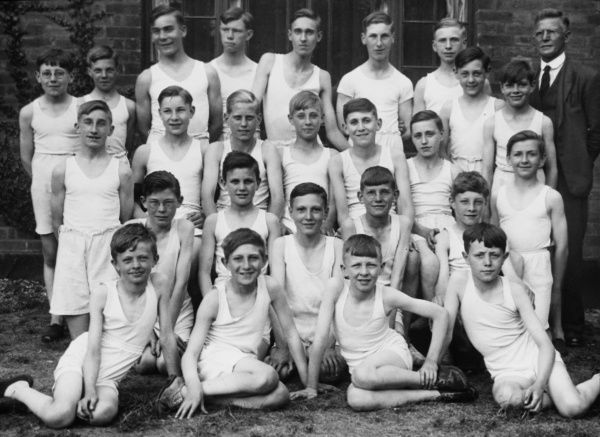 An formal gym class group photograph featuring 25 boys from a Boys Club of 1933, standing and sitting outside, with their club leader standing proudly to the right