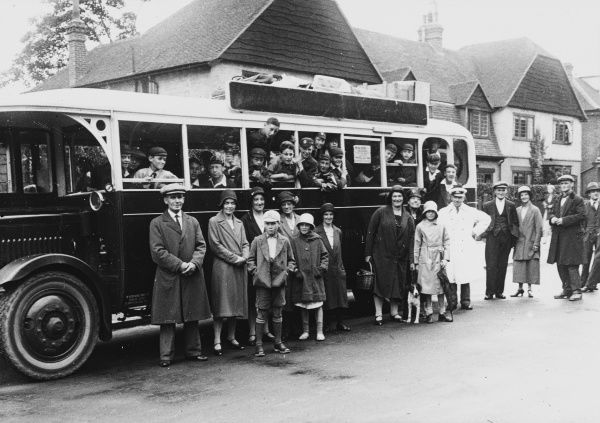 A group of happy exited young members of a boys club say their farewells to their families before boarding a bus, taking them for a week of camping and adventure in the countryside. They pause for a photograph