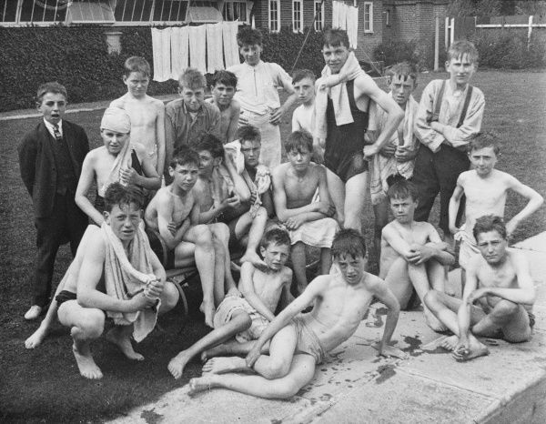 Boys from a Boys Club sit after their swim by the edge of a swimming pool