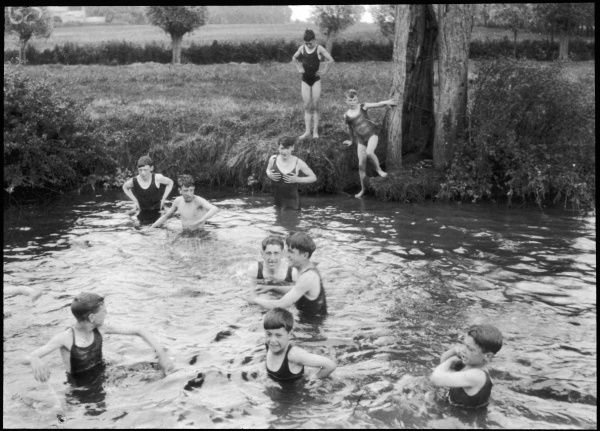 A group of ten boys from a Boys Club take an afternoon swim in a river, doubtlessly cold. All wear one piece costumes. Two boys on the bank look slightly apprehensive