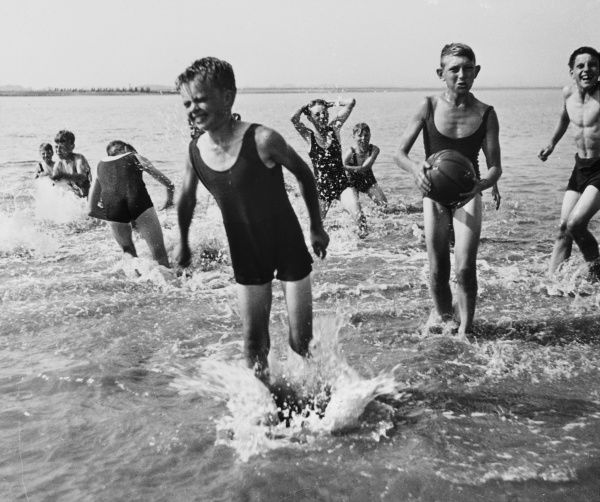 A group of boys from a Boys Club take their afternoon exercise in the sea, swimming and splashing All have one piece costumes and one boy has a ball