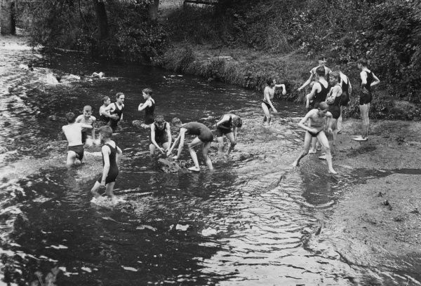 A group of boys from a Boys Club take a swim in a river, doubtlessly cold. Most wear one piece costumes