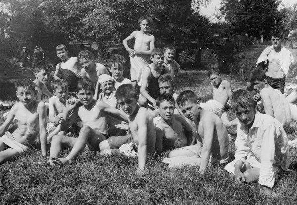 A group of boys from a Boys Club sit by a rivers edge and dry off in the sun after their swim