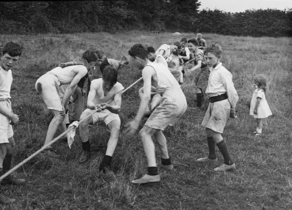 One half of a tug of war with members of a Boys Club. Their supporters shout encouragement and one small girl look on bewildered