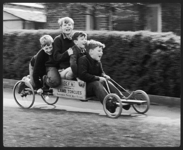 Four boys on a home-made go-kart made out of a box which once contained frozen lamb tongues, in Horley, Surrey. Two of the boys are the photographer's own and they are all having fun