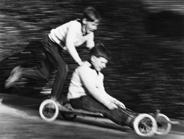 Two boys enjoying a ride on a home-made go-kart in Horley, Surrey. They are travelling at such a speed that the photograph is blurred!