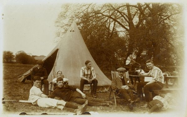 A group of boys and men relaxing on a camping holiday, with a wind-up gramophone to keep them entertained