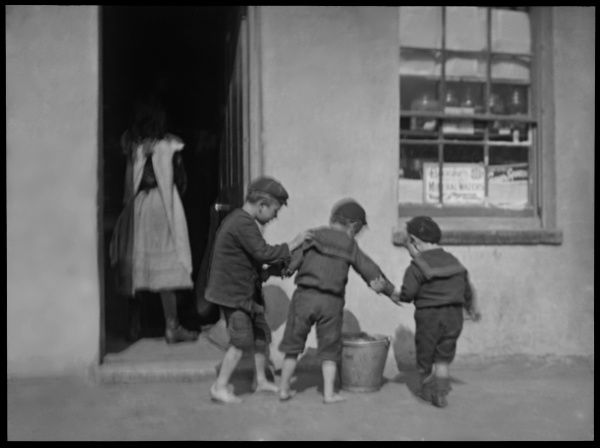 Three boys, two of them with bare feet, standing on a pavement outside a shop with a metal pail