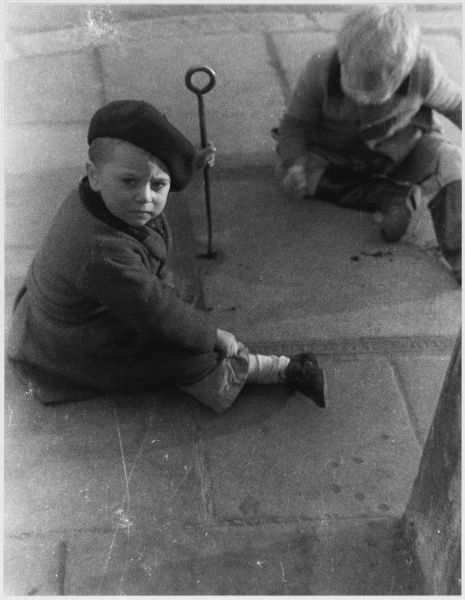 Two young boys sit and play on the pavement