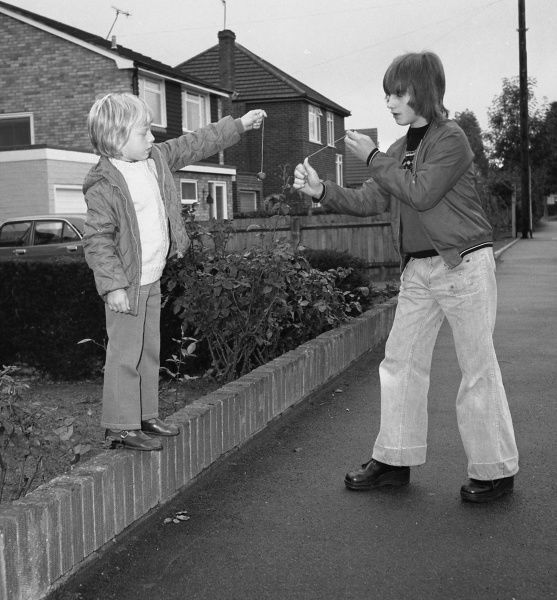 Two boys playing conkers on a suburban street