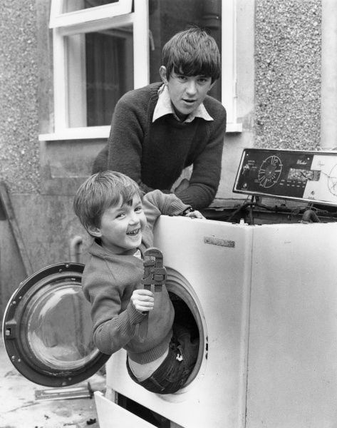 Two young lads fooling about with (and inside!) an old washing machine. Perhaps they were harbouring dreams of a career in plumbing at this stage?!