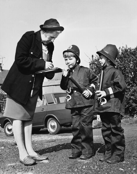 'Erm, excuse me Missus, ain't we supposed to be arresting you?' Two boys dressed up as policemen look perturbed when an old lady with a whistle starts to jot in her notepad. Date: 1960s