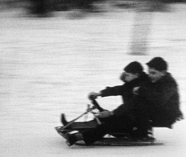 Two boys speed along on a sledge in the snow. Date: circa 1960