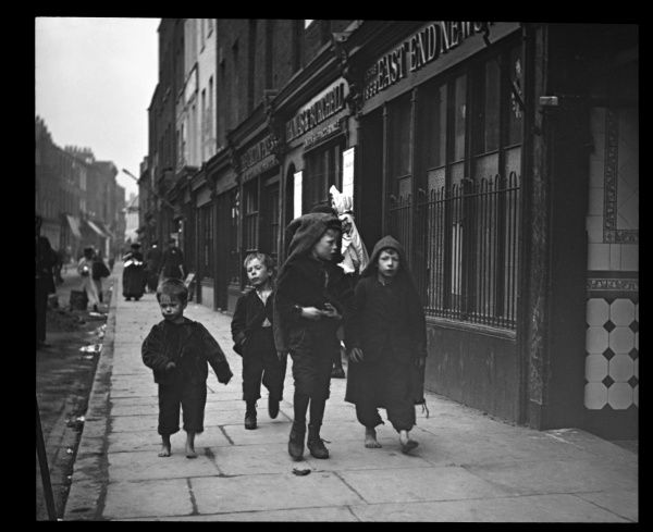 Four boys walking along a street in the East End of London, passing the premises of the East End News. Two of them have bare feet. Two are wearing hoods, though it doesn't appear to be raining