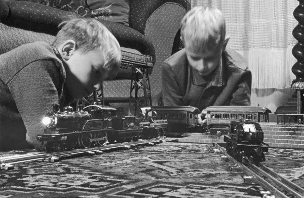 Two blond boys are absorbed by their model train set