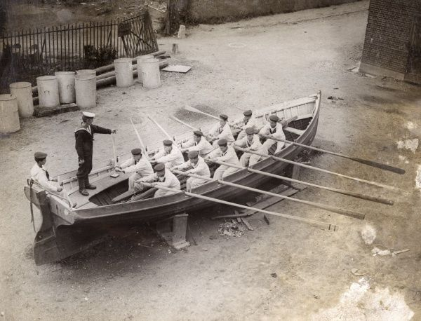 Boys in training, receiving their first lesson in oarsmanship at Shotley Barracks during the First World War. They are naval cadets attached to HMS Ganges, a Royal Navy training ship. Date: 1914-1918