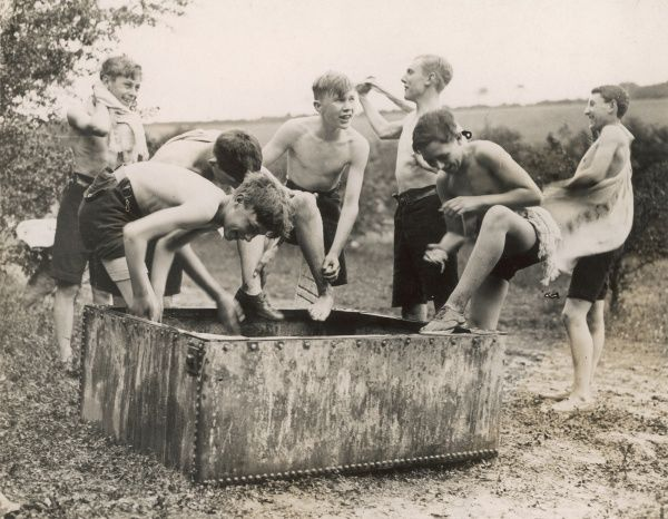 A cheerful group of boys on a summer camp find a trough in a field for their evening wash