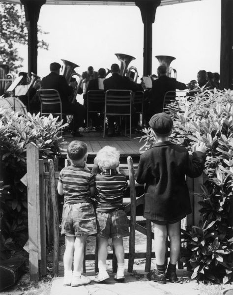 Three little boys stand behind a picket gate and watch a brass band playing in a bandstand