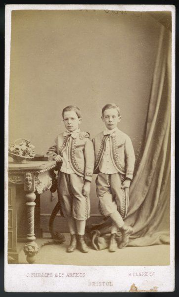 Two boys in knickerbocker suits with Zouave jackets ornamented with decorative braid also bowties, light coloured waistcoats, socks & boots