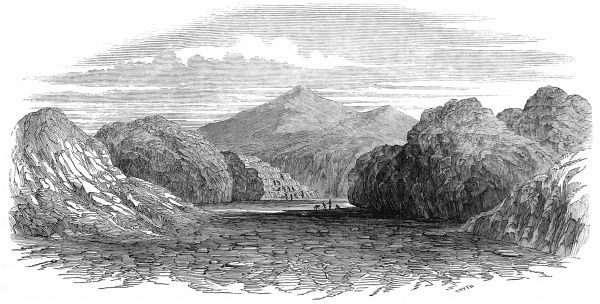 An engraving of a rocky and mountainous region with a wide river running through it, in the distance men are washing ore in the river propecting for gold