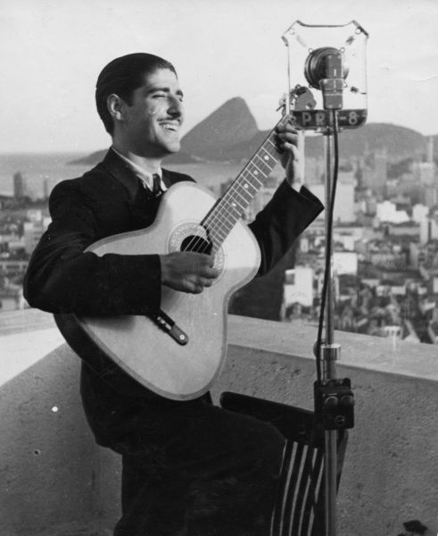 A crooner of Rio de Janeiro, Brazil, South America, singing into the large microphone and strumming his guitar Radio Rio. Date: 1930s