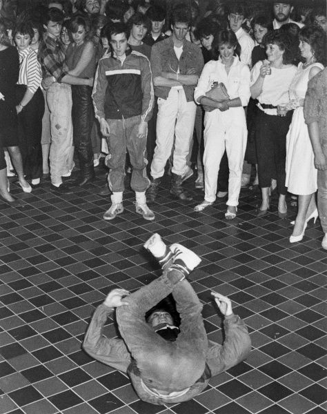 A breakdancer spins round on his back and stuns his teenage onlookers. Note the profusion of of white clothes and stilettos, slip-on shoes with white socks, perms and mullets