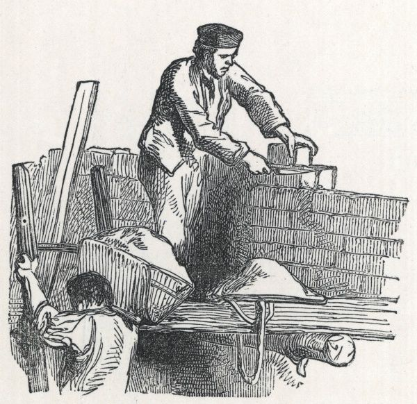 Two builders bricklaying: the hodman carries cement up to the bricklayer positioning bricks to build a wall