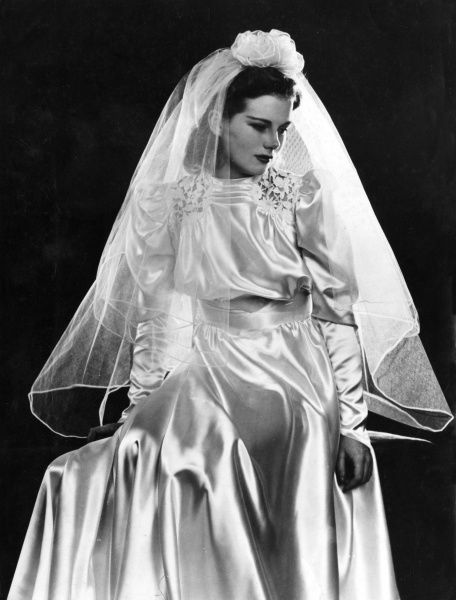 Bridal fashion : The cutwork embroidery on the shoulders is a pretty feature of this simple wedding dress. Date: 1930s