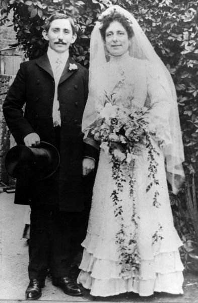 A happy English bride and groom. He, sporting a moustache, has removed his top hat to have his picture taken. She holds a splendid bouquet of flowers. Date: 1890s