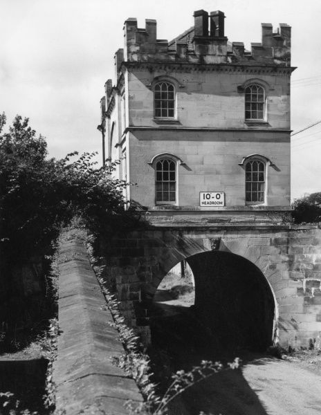An unusual bridge, near Mostyn, Flintshire, Wales. Two houses are built on a bridge, which also bridges another road on the Mostyn Estate. Date: 1960s