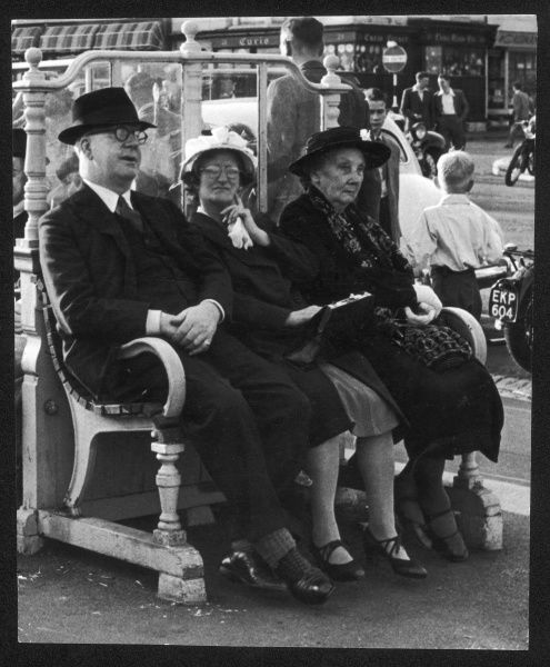 Three smartly-dressed elderly people, all wearing hats, sit on a bench in Brighton and survey the scene Date: circa 1953