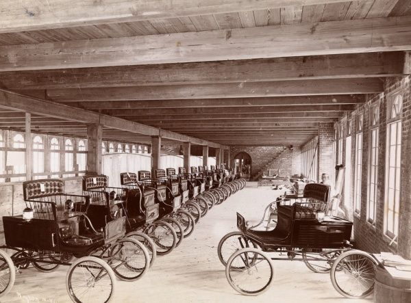 Autos, Mobile Auto Factory (Brisben Walker) Builder & Proprietor. Automobile factory at Kingsland Point, Hudson River (near Tarrytown, NY) with a row of automobiles lined up in lon
