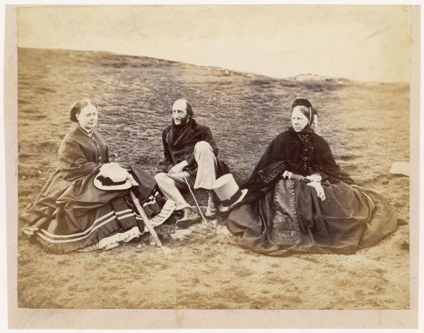 A gentleman and two ladies rest after a walk in the country