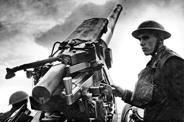 Photograph showing a British anti-aircraft gunner, with his hand on the trigger of his 3.7-inch gun, somewhere in Britain, c.1940