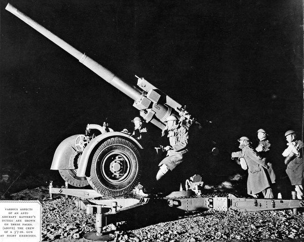 Photograph showing a British 3.7-inch anti-aircraft gun taking in part in night exercises, somewhere in Britain, c.1940