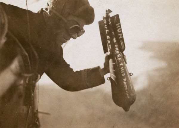 A British airman dropping a bomb by hand, in midair, during the First World War. The message on the bomb reads: Hun, Bulgar, Share This Ration. Date: 1914-1918