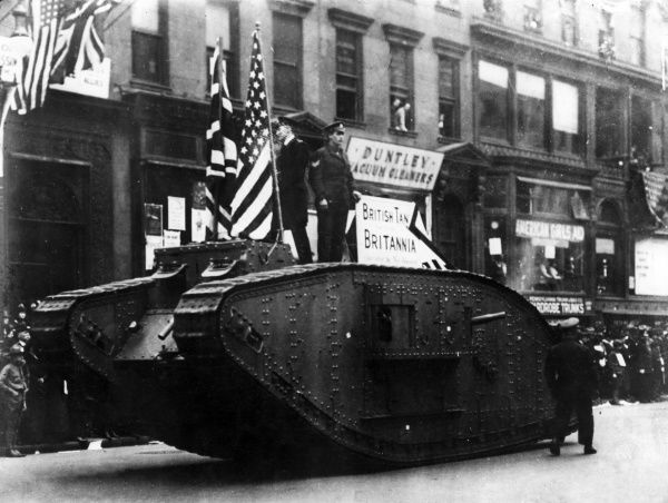 British and American soldiers standing on top of a tank, with their respective flags, in a street procession during the First World War. Date: early 1918