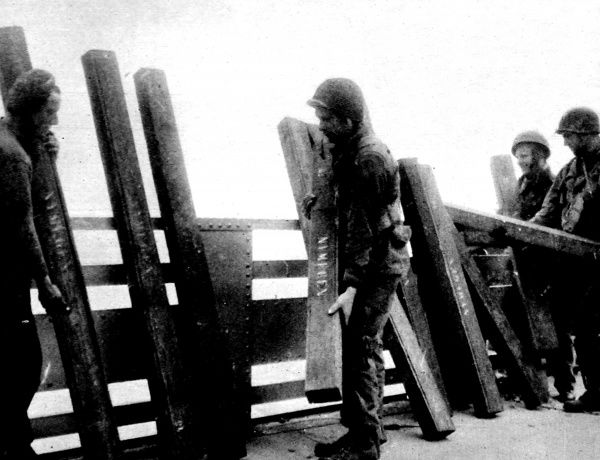Photograph showing British and American troops stacking dynamite charges against the railing of Nijmegen Bridge, September 1944. As the Allied army advanced towards Nijmegen, the German general defending the town put 10,000 lbs of explosives on the bridge